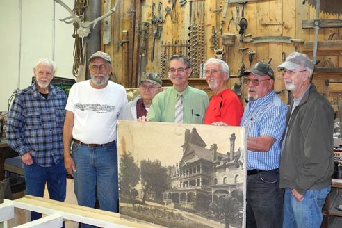Paso Robles Mayor Steve Martin poses with the Pioneer Museum team working on a scale model representation of a portion of the front of the original Paso Robles Inn.