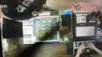 Partial photo of suspect showing sweatshirt and handgun.