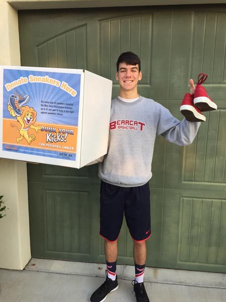 Dante Coletta holding one of the collection boxes for Dunk Your Kicks fundraiser.