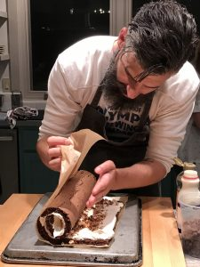 Chef Veatch expertly rolling the cream-filled sponge cake into a log shape