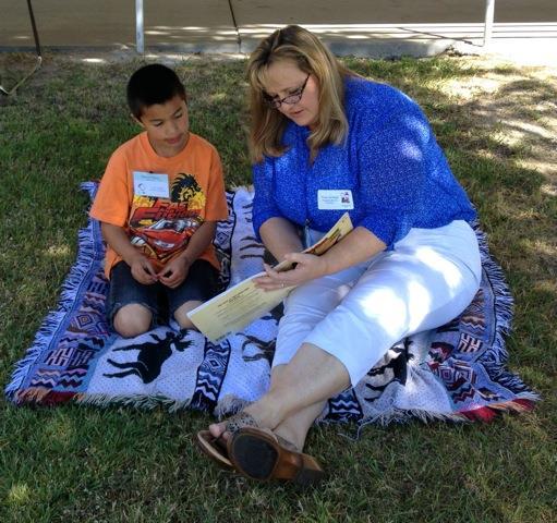 Student Alejandro Ibarro enjoys a story with Trina Nicklas.