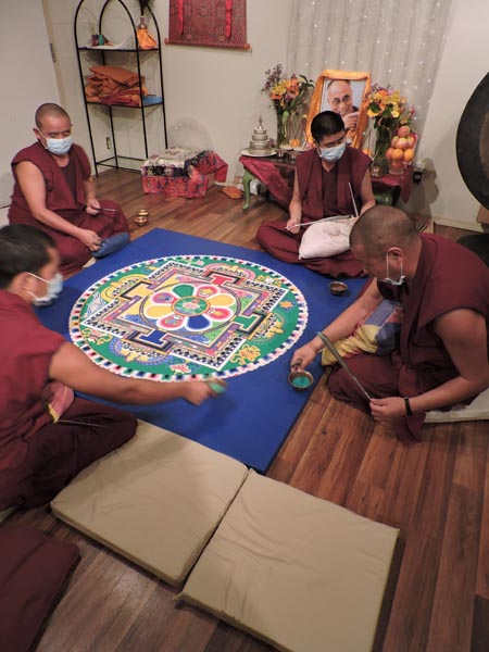 The monks lay the finishing touches on the mandala.