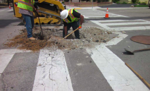 Here the contractor is lowering all the utility covers in preparation of the paving work.