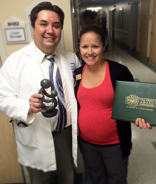 """Twin Cities Community Hospital DAISY Award recipient Summer Garcia, (right), accepts the honor for """"Extraordinary"""" skills and care with Sergio Toledo, MD, Twin Cities hospitalist (left) before her fellow nurses and Twin Cities Community Hospital staff."""