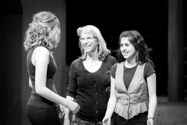Catherine Kingsbury works with two student actors onstage.