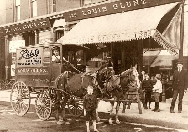 Louis Glunz II, circa 1900, standing next to the horse in front of the family's wine store on Wells St. in Chicago.
