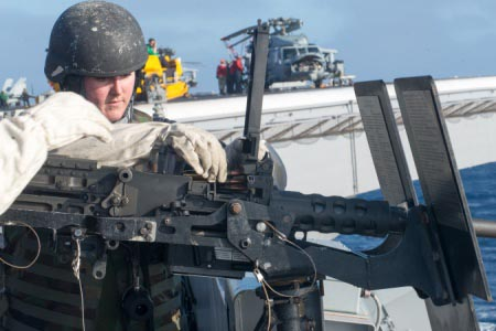 Aviation Ordnanceman Airman Amber Deranek, from Paso Robles, Calif., reloads a .50 cal machine gun during a live-fire exercise aboard USS John C. Stennis (CVN 74).