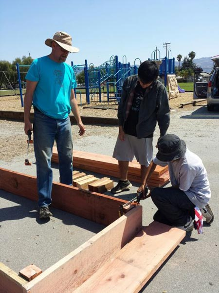 A member of Big Creek Lumber supply helps schoolchildren construct a redwood bed for the school garden.