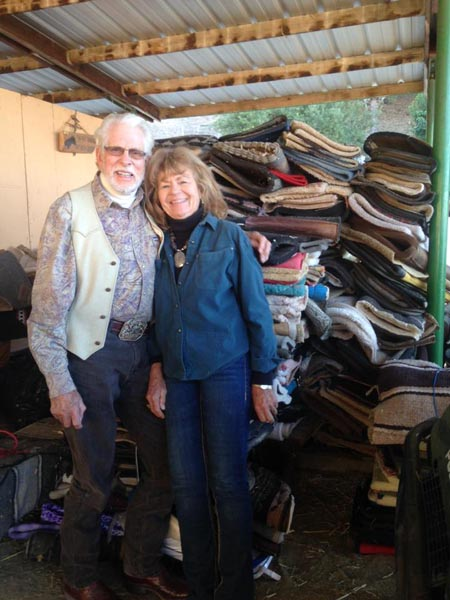 Dr. Gordon and wife Lu stand next to stacks of donated saddle pads waiting to be shipped to Haiti.