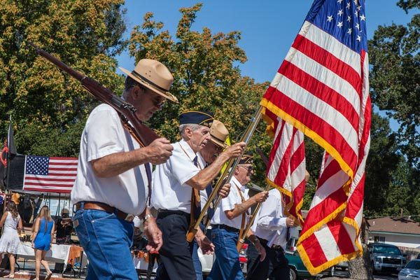 The parade began with spectators rising and removing their hats as the North County Veterans Color Guard and Honor Guard marched by with the flag. Photo by Rick Evans.
