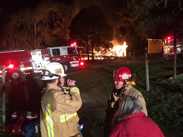Property owner Debbie Sullivan confers with fire officials while a 120-year-old home on her property burns. Photos by Dick Mason.