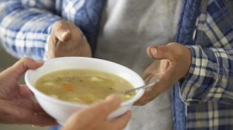 Woman giving bowl of soup to man