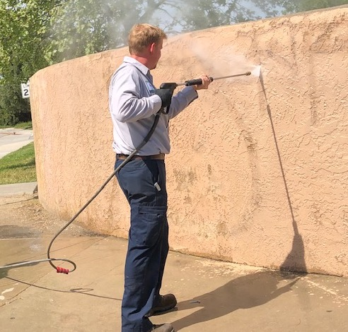 City cleans graffiti off wall on Niblick