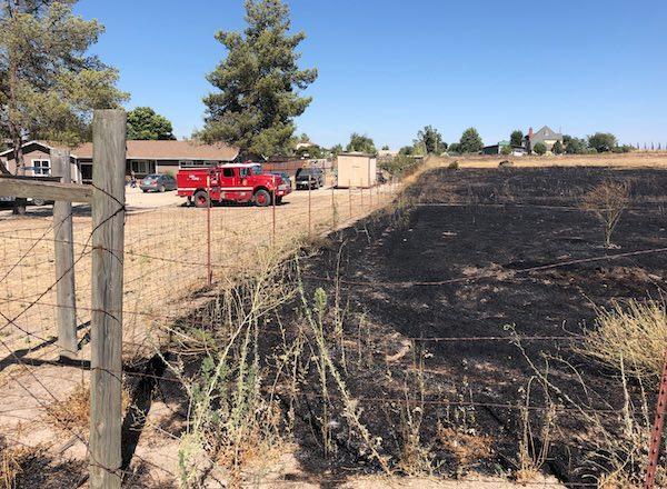 Fire that threatened two homes contained at one acre